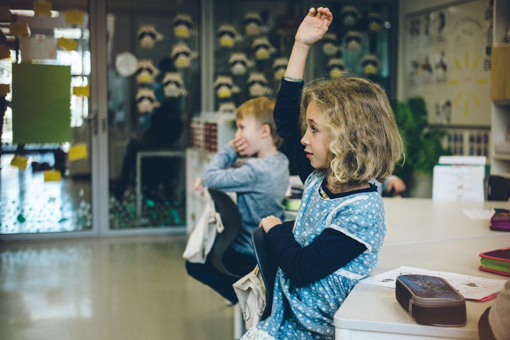 Kind in Schule hebt Hand